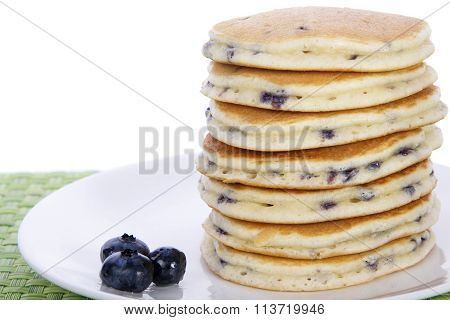 stack of blue berry pancakes on plate with three blueberries