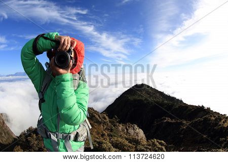 young woman hiker taking photo on  on mountain peak
