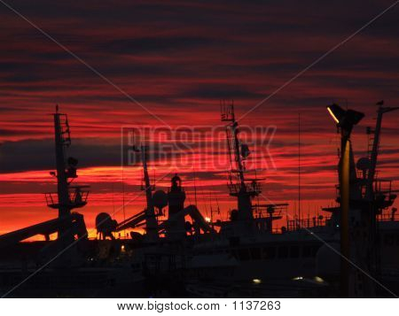 silouette harbour with fishing boats and sunrise
