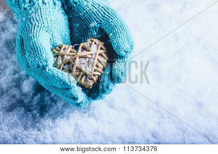 Female hands in light teal knitted mittens with entwined beige flaxen heart on a white snow winter background. Love and St. Valentines Day cozy concept. poster