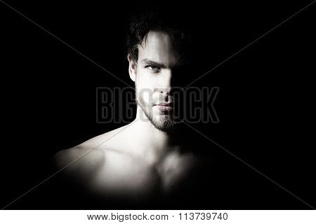 Closeup view portrait of one handsome bearded young macho man with strong look hazel eyes and sexy lips standing in light looking forward in studio on black background horizontal picture poster