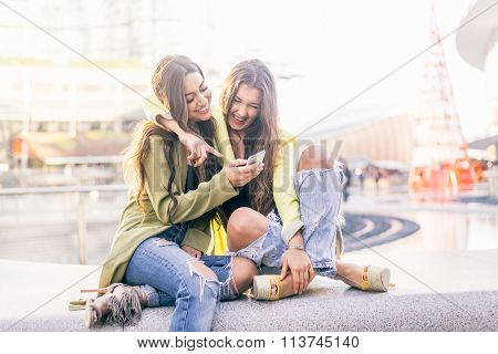 Girlfriends Looking Down At Smartphone
