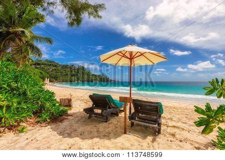 sandy beach with umbrella and beach chair at Seychelles