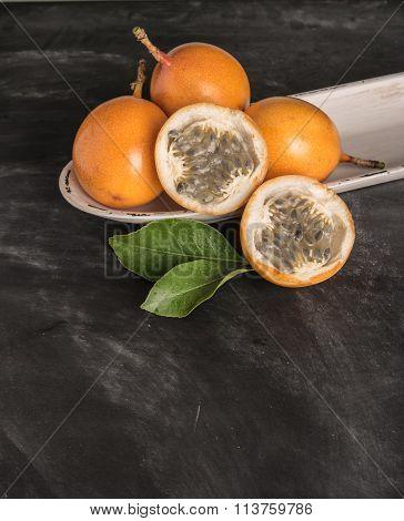 Fresh Granadillas On Slate With Leaves. Granadillas On Rustic Board