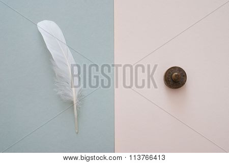 White Feather And Weight On Grey Paper Background