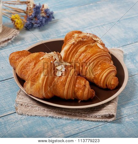 Two croissant with almonds on blue wooden surface. Delicious breakfast with fresh croissants. Top view. Square frame poster