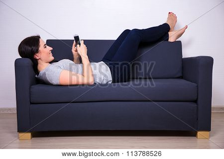 Happy Young Beautiful Woman Lying On Sofa And Using Smart Phone