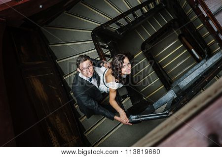 Couple posing on staircase.