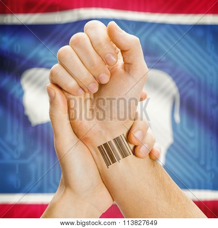 Barcode Id Number On Wrist And Usa States Flags On Background - Wyoming
