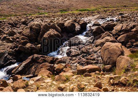 Stream Flowing And Splashing Among Bare Rocky Landscape