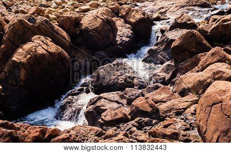 Stream Flowing And Splashing Among Bare Red Rocks