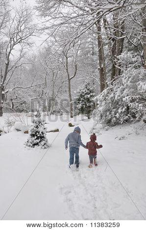 boy and girl walking through the snow