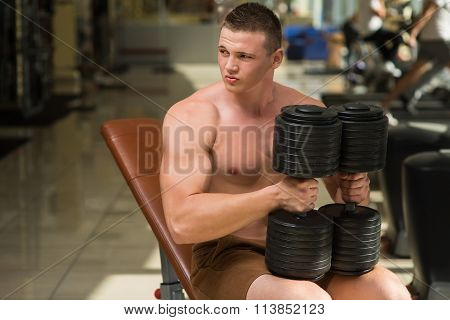 Sportsman posing on camera with dumbbells.