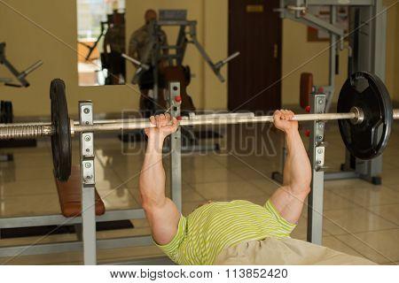 Bodybuilder lifts weights.