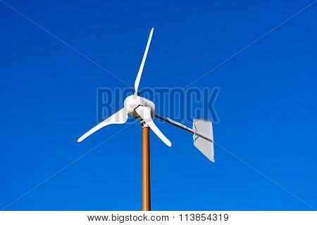 Small Wind Turbine On Blue Sky