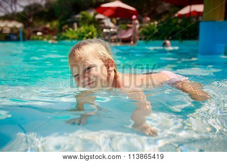 Small Blonde Girl Stands On Fours In Shallow Water Of Pool