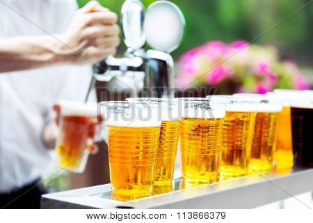 Man drawing beer from tap in an plastic cup. Draught beer. The bartender pours a beer in a plastic cup. On the bar table are plastic cups with a beer poster