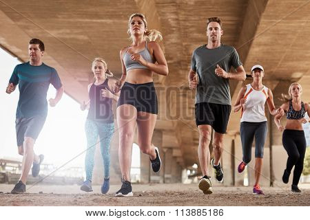 Determined group of young people running together in city. Low angle shot of running club members training together in morning under a bridge. poster