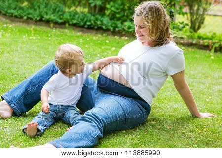 Pregnant woman and adorable little toddler son in garden.