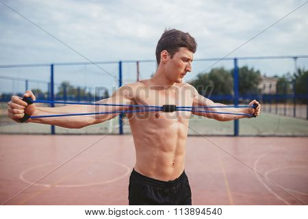 strong athletic guy sports man stretches expander