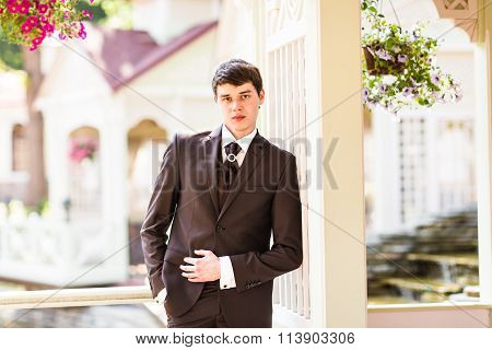 Portrait of the groom in a park on their wedding day.