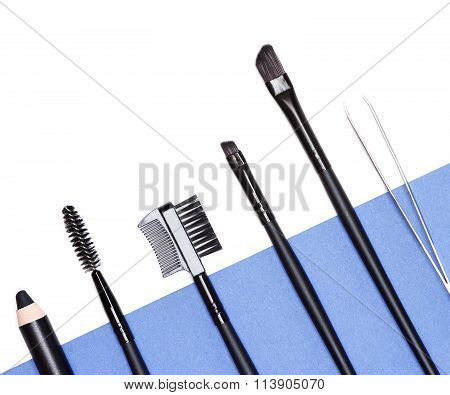 Accessories for care of the brows: eyebrow pencil angle brushes made from natural bristles spooly brush tweezers and brow comb / brush combo on white and blue background. Eyebrow grooming tools poster