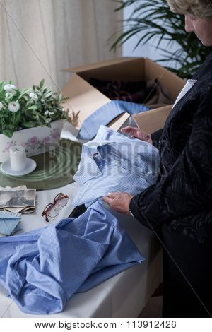 Picture of miserable senior widow packing things of her husband poster