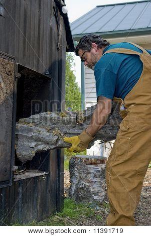 Man Loading Outdoor Wood Boiler