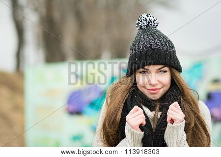 Young woman in black beanie and scarf outoors in winter