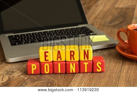 Earn Points written on a wooden cube in a office desk