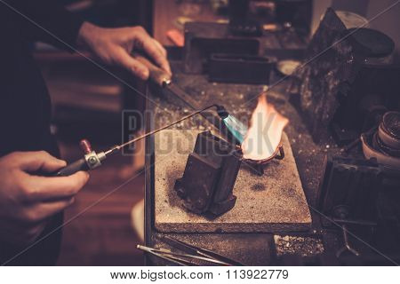 Goldsmith melting gold to liquid state in crucible with gasoline burner.