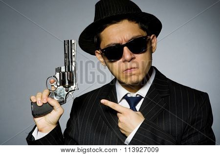Young man in classic striped costume holding gun isolated on gra
