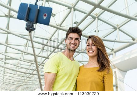 Young caucasian couple use selfie stick for taking photo together
