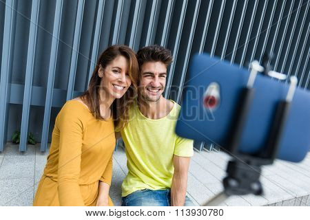 Young caucasian couple use selfie stick for taking photo