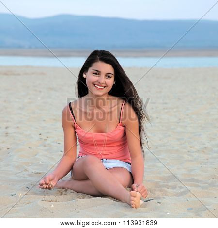 Young female teenager with long dark hair smiling and sitting on a sandy beach.