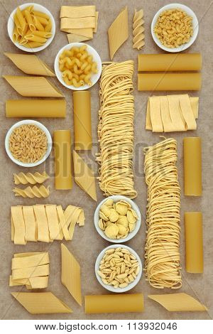 Italian pasta sampler forming an abstract background over natural hemp paper background.