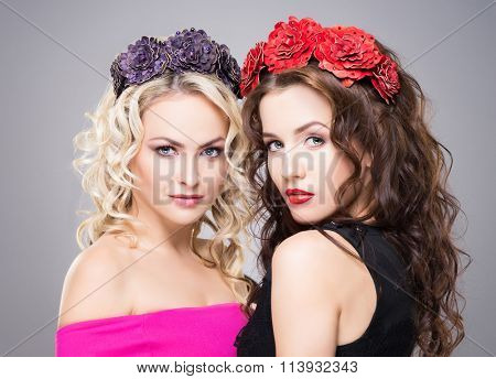 Beautiful, sensual blond and brunette wearing flower alike coronet over grey background.