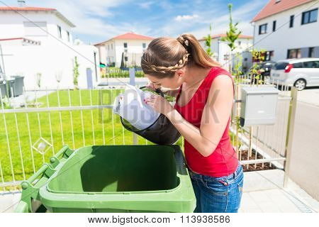 Woman throwing waste paper away in container