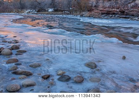 winter dusk over mountain river - partially froze Cache la Poudre River at Belvue near Fort Collins, Colorado
