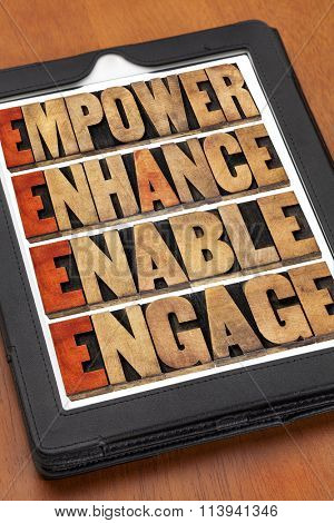 empower, enhance, enable and engage - motivational leadership and business concept - a collage of words in letterpress wood type on a digital tablet