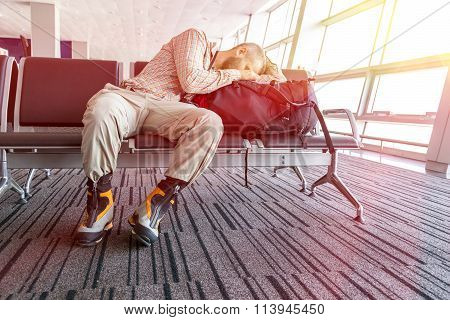 Canceled flight Man sleeping on his travel luggage