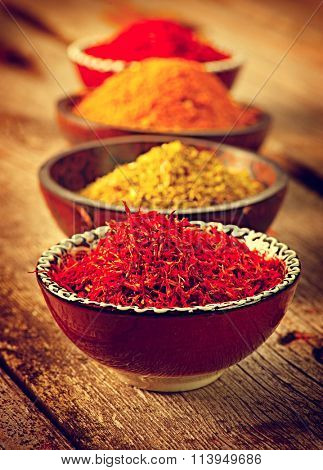 Spice. Various Spices over Wooden Background. Saffron, turmeric, curry in bowls on wooden table