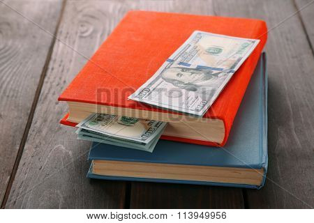 Books with nested dollar banknotes on wooden table. Stash of money