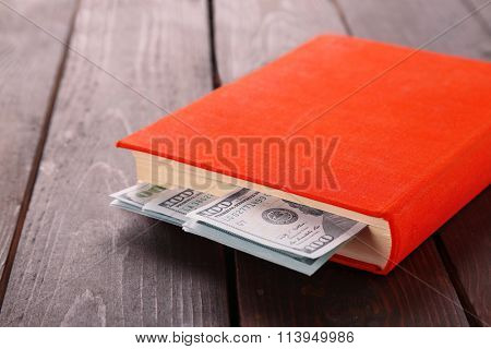 Red book with nested dollar banknotes on wooden table. Stash of money