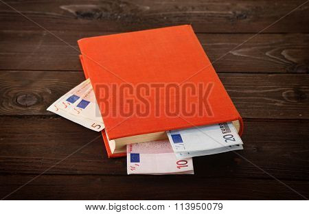 Book with nested euro banknotes on wooden table. Stash of money