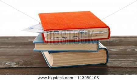 Books with nested euro banknotes on white background. Stash of money