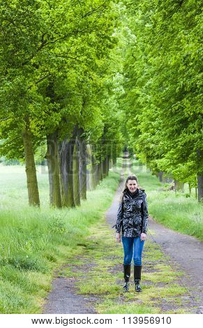 woman wearing rubber boots walking in spring alley poster