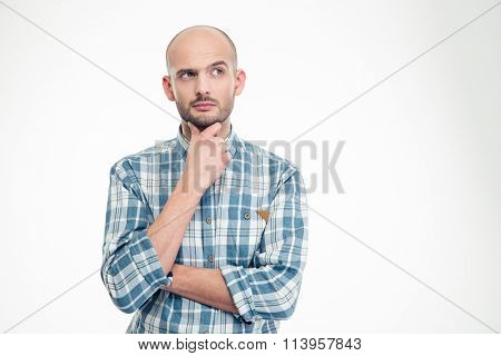 Attractive thoughtful young man in plaid shirt looking away over white background