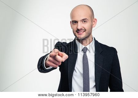 Attractive cheerful young business man in formalwear pointing on you over white background