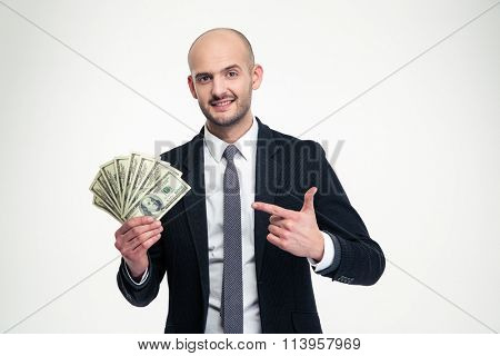 Confident attractive young businessman holding and pointing on money over white background